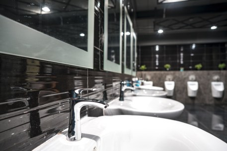 A commercial office's bathroom sinks and urinals.