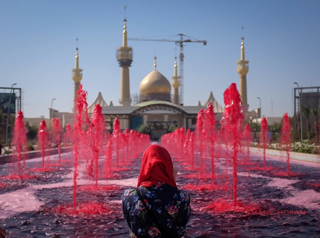 Woman looks over the fountain stained red at the mausoleum of Imam Khomeini, Tehran, Iran