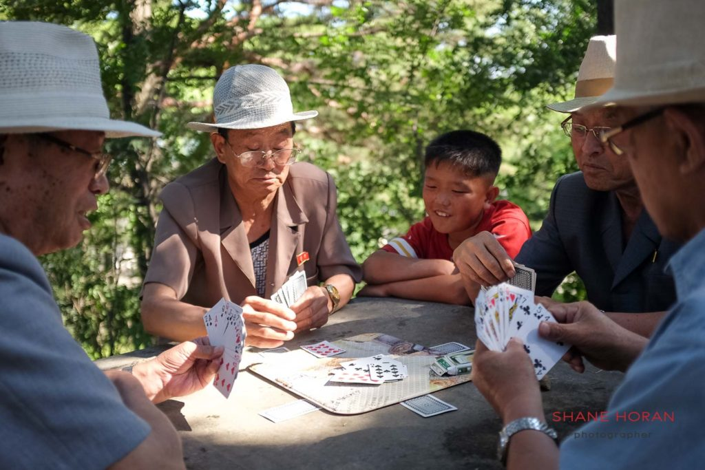 Men and boys enjoying a card game in Moranbong park, Pyongyang, North Korea