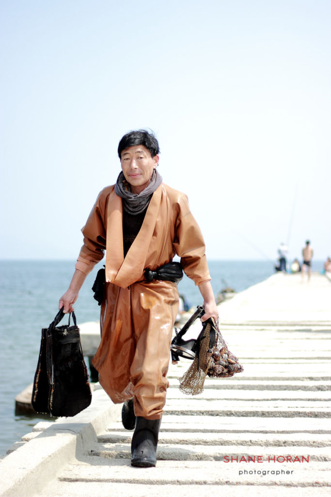 Clam fisherman emerges from the sea having collected for the day at Wonsan pier, North Korea