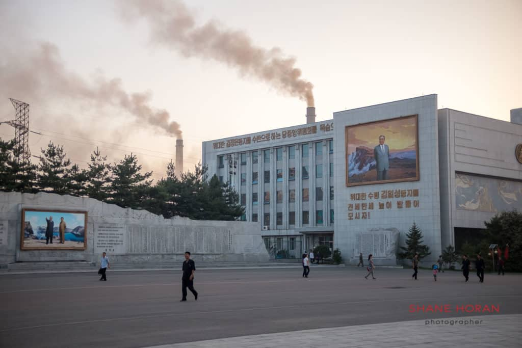 Pyongyang thermal power station seen behind a portrait of Kim Il Sung at the Mansudae art studio. North Korea