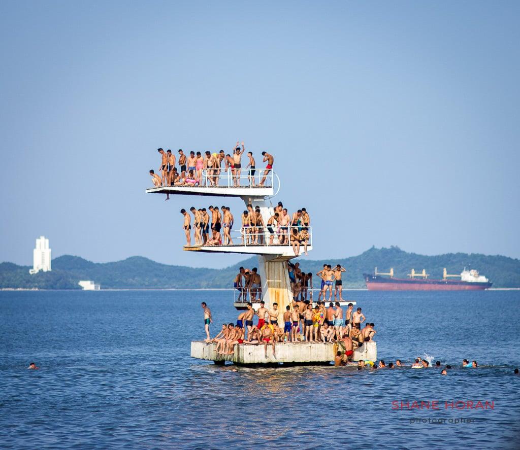 Locals crowd the diving platform at Wonsan Beach, North Korea