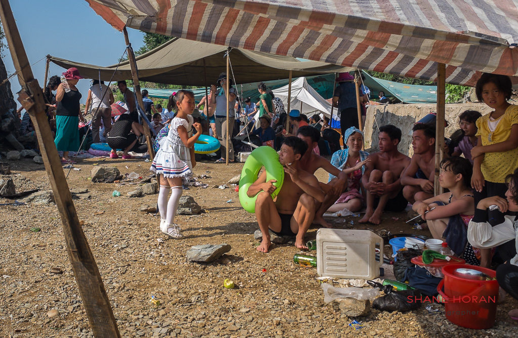 Girl entertaining her family at Nampo beach, North Korea
