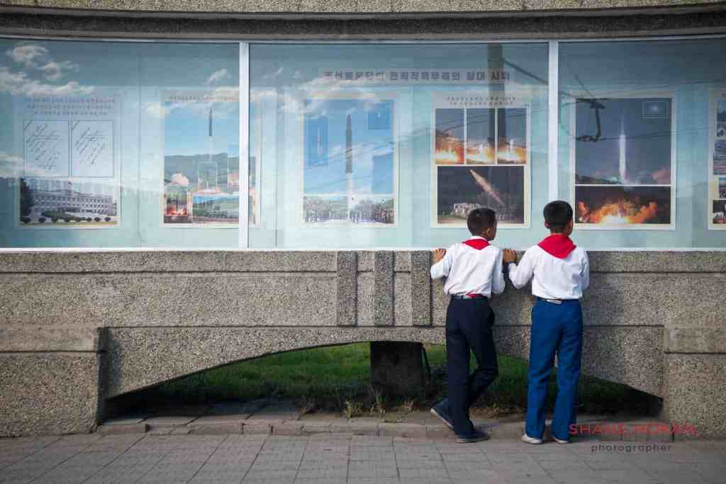 Young Pioneers take interest in news of recent rocket launches. Chongjin, North Korea.