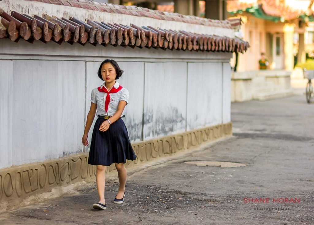 School girl walks along folklore street, in Sariwon, North Korea