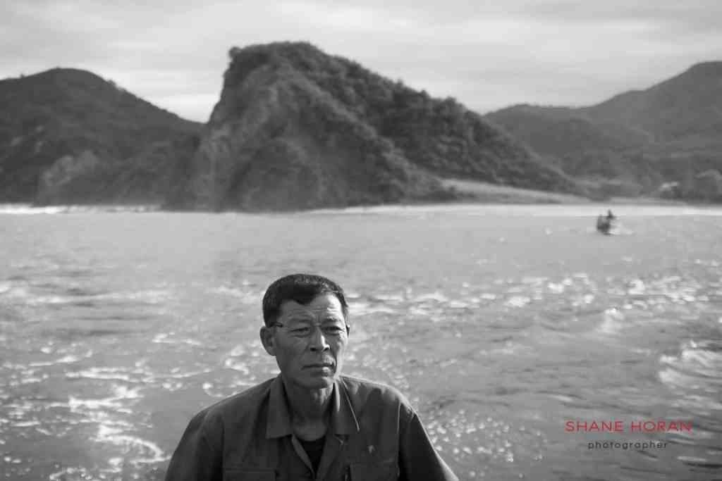 Fisherman steering his boat at Sea Chilbo, North Hamgyong, North Korea