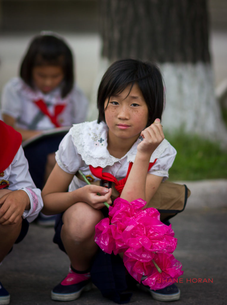 School child on a Kaesong street waiting for the arrival of delegates from the Children's union to arrive in the city. North Korea