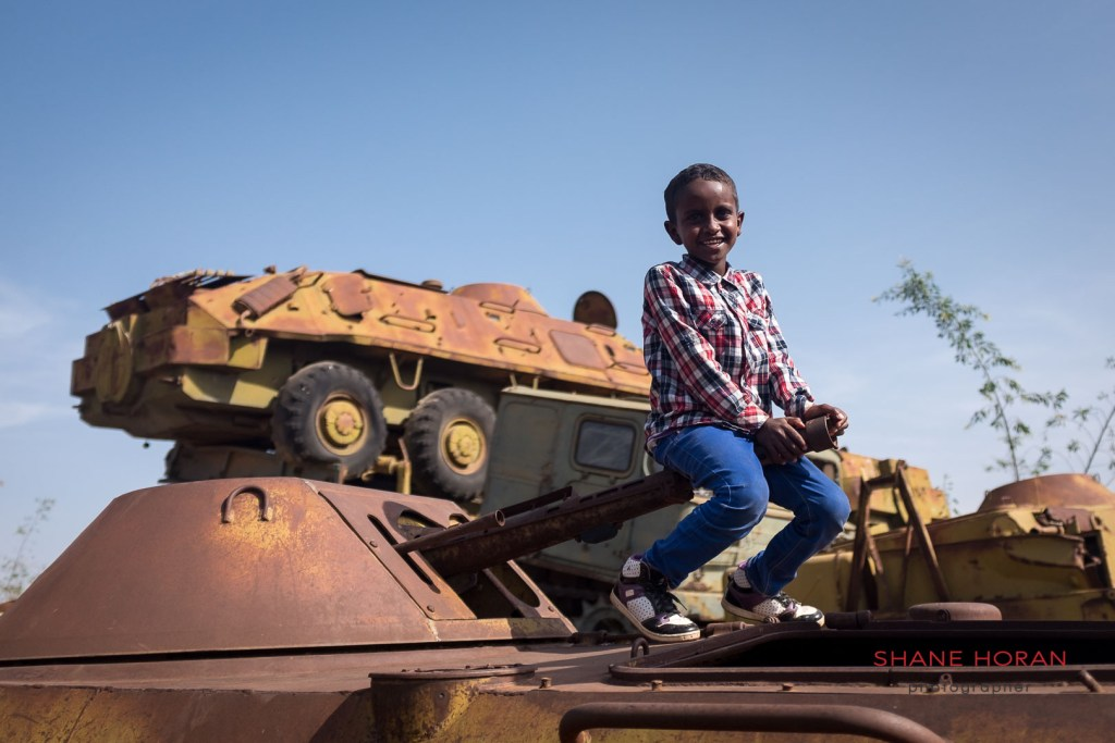 Local kid poses on a rusting tank, Asmara, Eritrea
