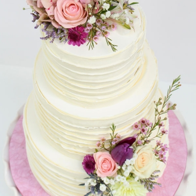 Ruffled buttercream wedding cake with fresh flowers