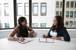 Two black women sitting at a white table. Both are writing in a notebook and discussing what it means to bet on yourself.