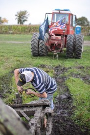Logan Douglas, age 16, hooks up the truck to the tractor for his Step Father, Doug Jarman, to tow him out of a mud pit in Farwell, Mich. on Friday Oct. 4, 2013.