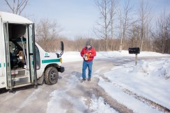 Bill walks from the mailbox after arriving to his house in Farwell, Mich. on the I-Ride Monday morning, March 24, 2014.