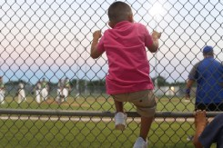 Four year old, Jordan Ybarra climbs the fence as the two teams change after an inning on the Roy High Field at the Victoria Youth Sports Complex.