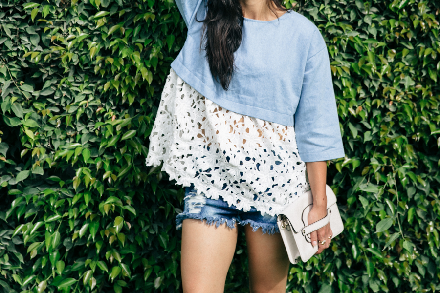 Dahlia Boutique Charlene oversized chambray blouse with floral lace trim. Frayed denim shorts for summer outfit.