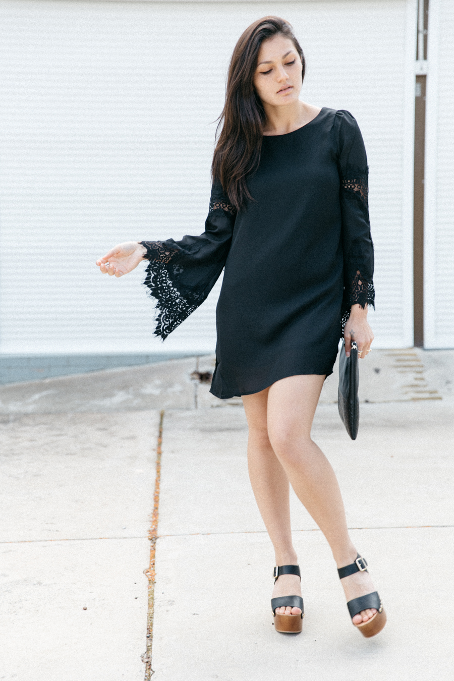 Black bell sleeve dress with lace panels.