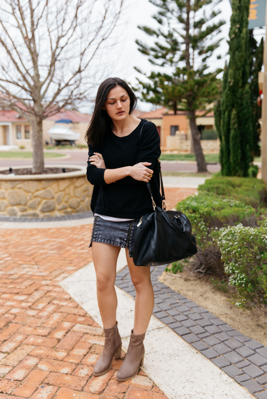 Black sweater with skirt & leather boots.
