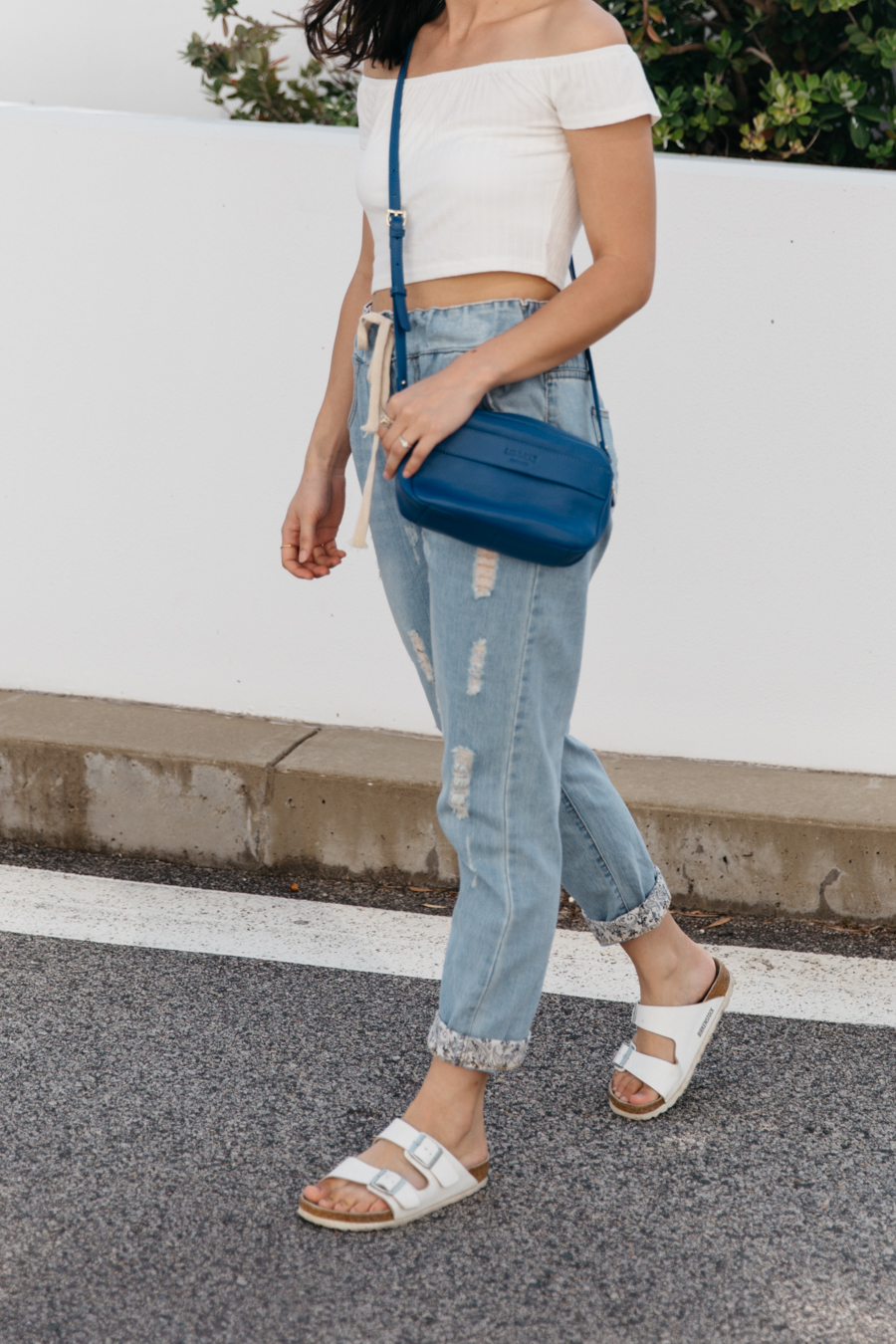 Small blue shoulder bag with boyfriend jeans.