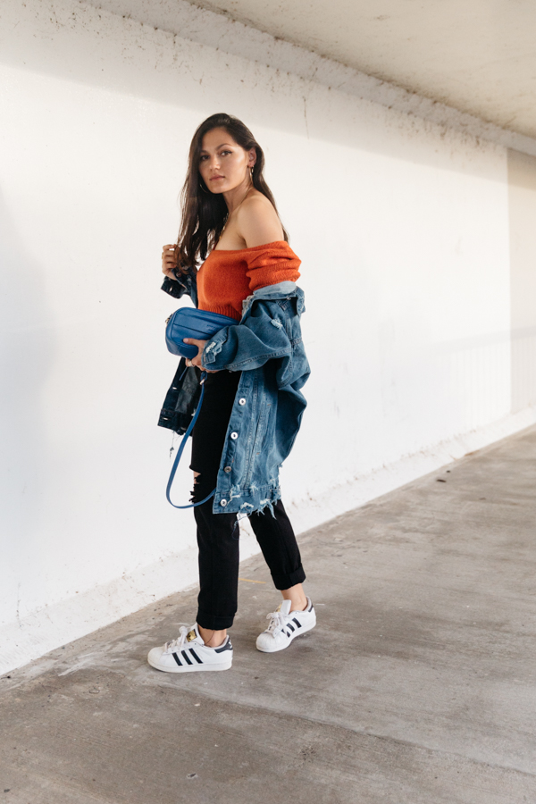 Orange outfit with denim jacket and black mom jeans.