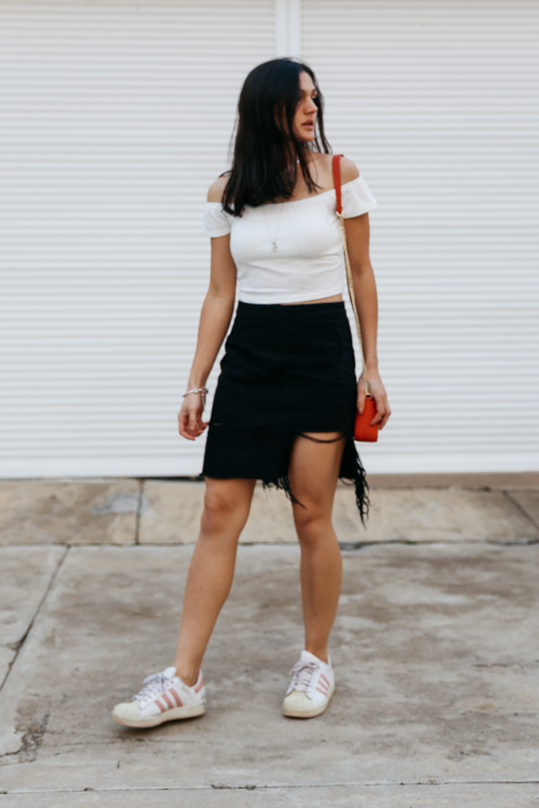 White crop top with black denim skirt and Adidas Superstar sneakers.