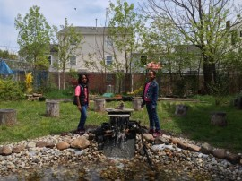Neighborhood children posing next to a water fountain