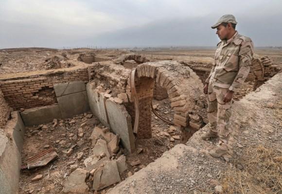 Soldados hacen guardia sobre las ruinas dañadas de un sitio de la antigüedad (© AP Images)