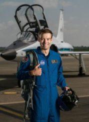 Robb Kulin en traje de vuelo delante de un avión (NASA)