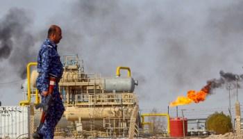 Un oficial de policía hace guardia en una estructura procesadora de petróleo y un pozo petrolífero en llamas (© Essam Al-Sudani/Reuters)