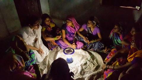 Mujeres sentadas en torno a una luz solar, en la India (© Frontier Markets)
