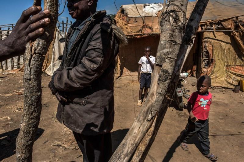 Dos niños y un hombre de pie entre unas ramas y chozas (© Michael Robinson Chavez/Washington Post/Getty Images)