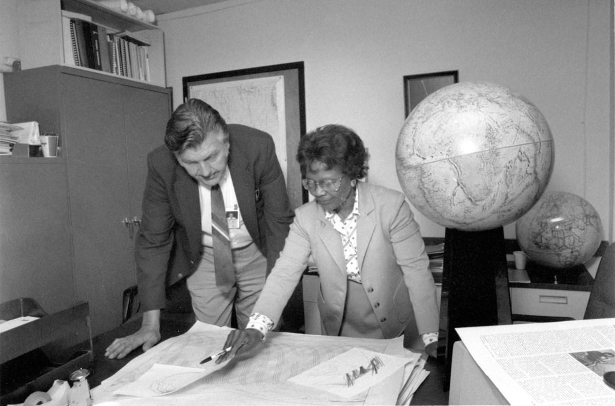 Hombre y mujer mirando mapas sobre una mesa (U.S. Navy)