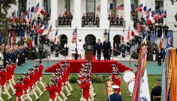 Una banda marcha en el Jardín Sur de la Casa Blanca mientras los presidentes Trump y Macron, sus esposas y otros observan (© Evan Vucci/AP Images)