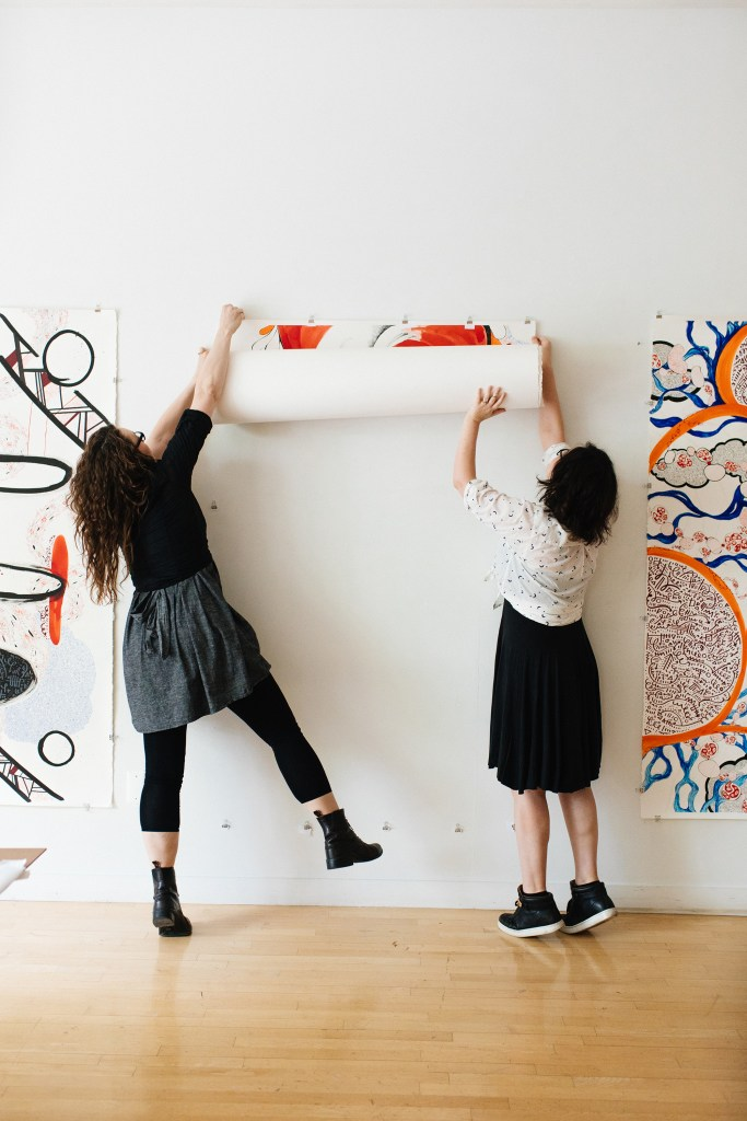 Fiona and Maria installing artwork