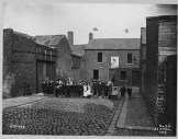 Boundary Street Area: Junction of Greenland Street at Gable Street left to right No.s 15 & 16 on plan Greenland Street. Streets in photo: Greenland Street, Gable Street, Boundary Street. Premises in photo: Mineral Water Co.'s premises. Poster reads 'Vote for Smiley'. PRONI Ref: LA/7/8/HF/3/25