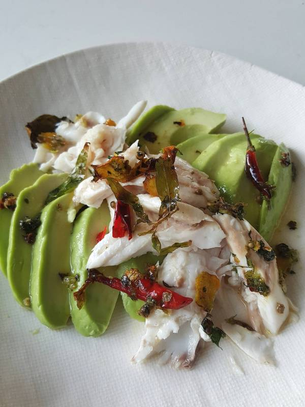 Baked fish with aromatics on avocado