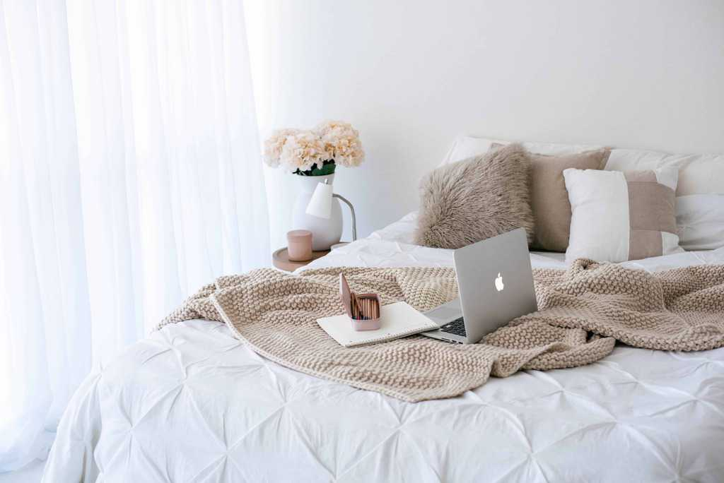 laptop and books and stationaries on the bed