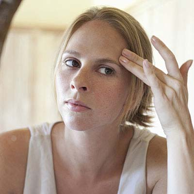 Woman looking in the mirror and wonders why her skin feels a little off