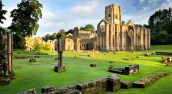 Sham ruins at Fountains Abbey, North Yorkshire. Remains of the monks' infirmary are visible in the foreground. The Cistercian community of monks was founded here in 1132 but was dissolved in 1539.