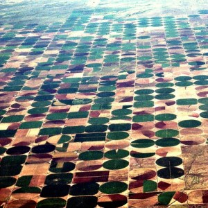 Center pivot irrigation in Kansas-Nebraska area from 30,000 feet. Massive sprinklers on long pipe segments pivot like a waterwheel to nourish crops...and create geometric imprint on the land.