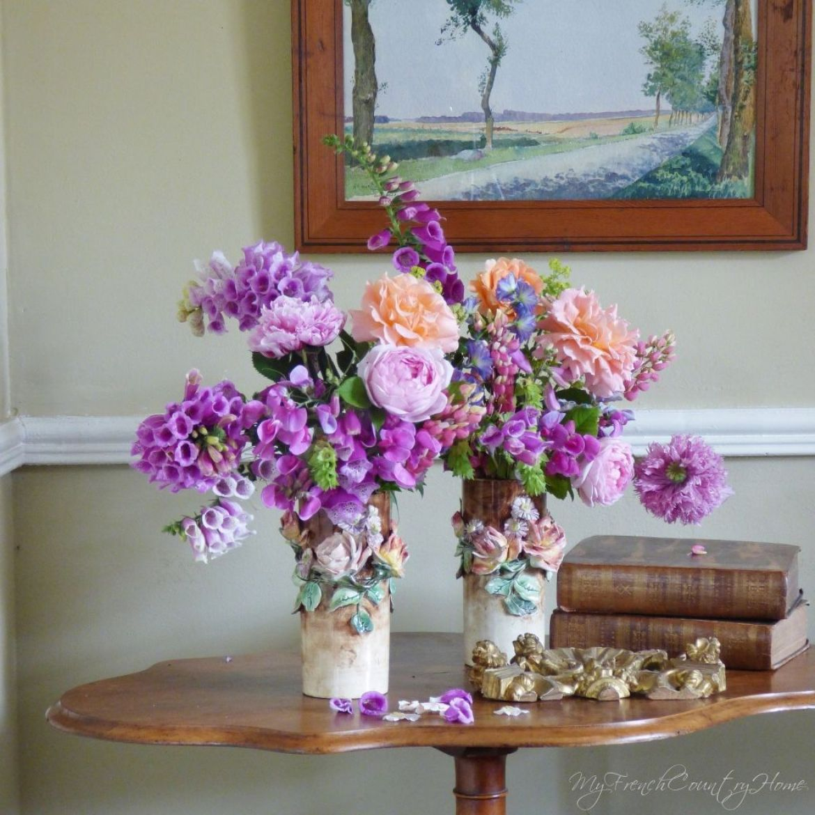 roses and foxgloves arranged in antique vases