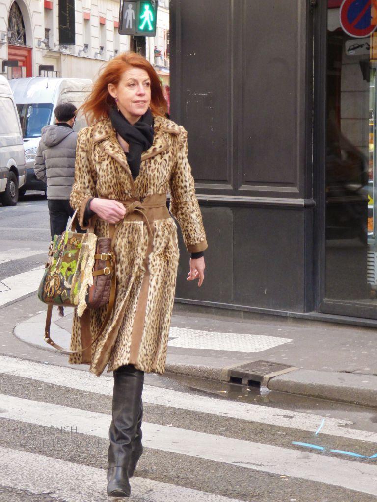 women in leopard skin caot crossing street in paris