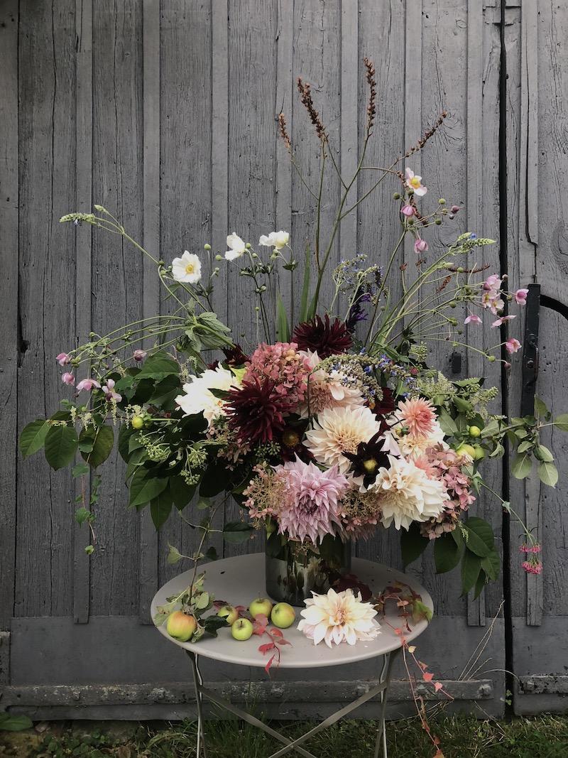 autumn flowers arranged in vase outside barn