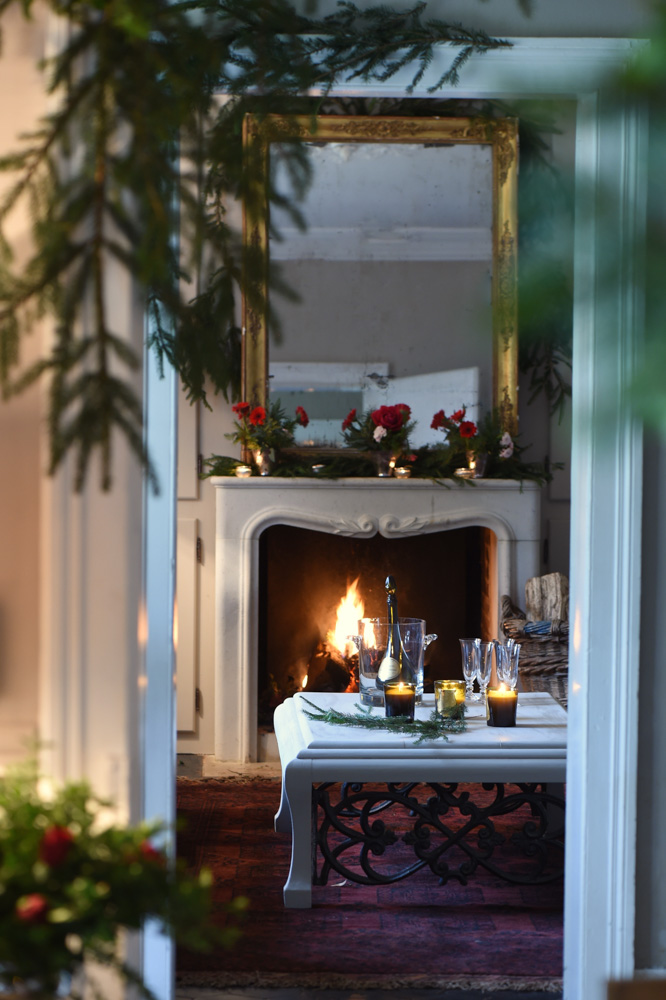 View into living room with marble fireplace and red flower decorations on the mantle- red christmas decoration ideas- MY FRENCH COUNTRY HOME