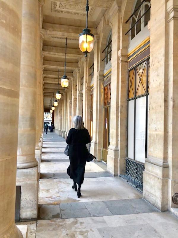 in true parisian style a woman walking through building in paris