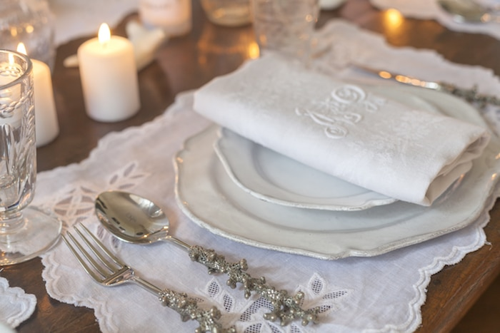 table laid with white china and napkins