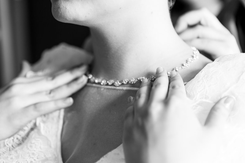 fastening necklace around bride's neck