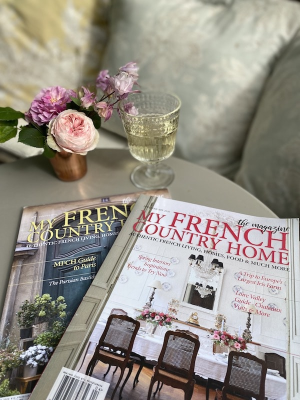two magazines on a table with flowers and champagne