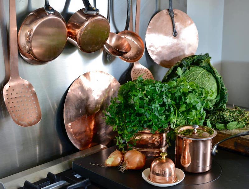 copper pans and utensils on stove