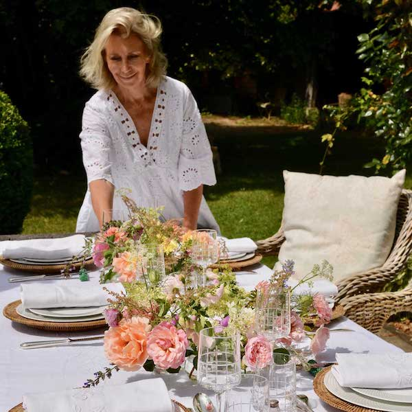 woman in white setting a table