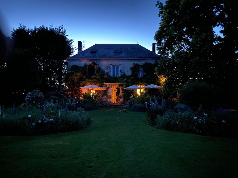 french country home at night with glowing windows