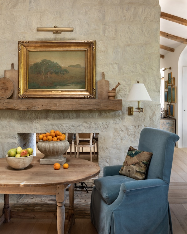 wooden kitchen table with bowls of fruit and a blue armchair